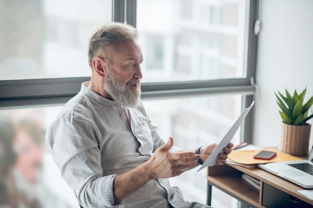自宅で仕事をし、書類を精査する成熟したビジネスマン