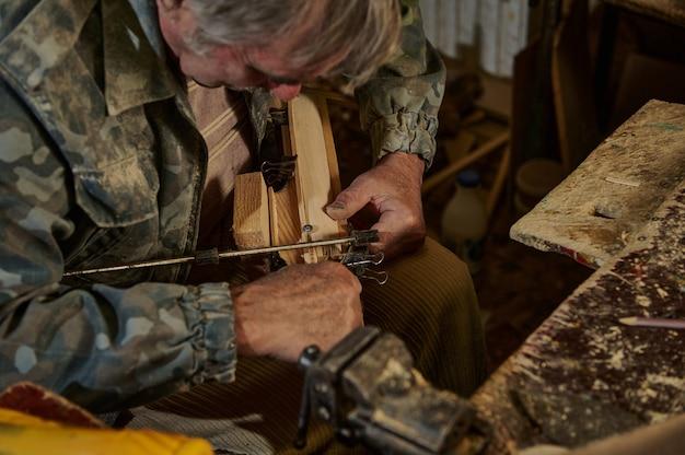 Зрелый плотник делает в домашней мастерской деревянную модель парусника. искусство, хобби, резьба по дереву, ремесленные концепции