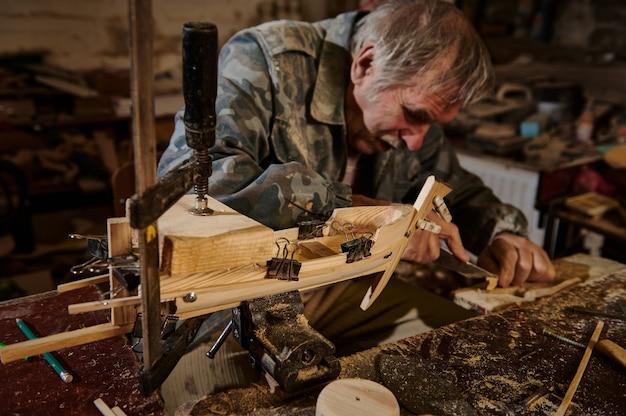 Зрелый плотник работает в своей мастерской над деревянным игрушечным парусником. ремесленник делает деревянные предметы ручной работы в своей мастерской.