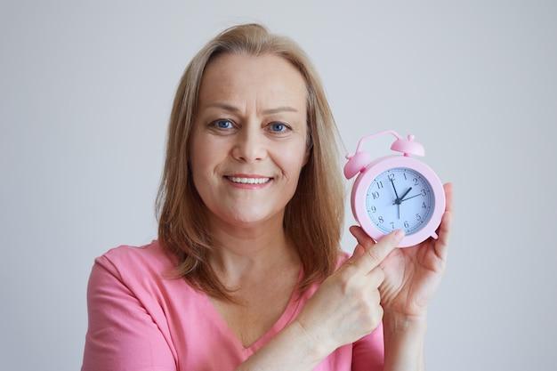 成熟した陽気な女性は、手に目覚まし時計を持って、楽しく時計の針を見せ、カメラをのぞき込みます。灰色の背景の写真