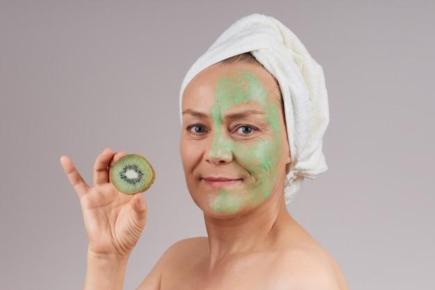 肩をむき出しにし、頭に白いタオルをかぶった成熟した陽気な女性は、顔に緑色のフルーツマスクを置き、手にキウイを置きます。フェイシャルスキンケアのコンセプト。灰色の壁を越えて。