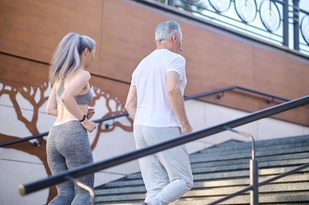 Пожилая пара вместе бегает по утрам и выглядит довольной