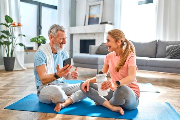 Пожилая пара отдыхает после тренировки, пьет протеиновый коктейль и пользуется телефоном дома. Premium Фотографии