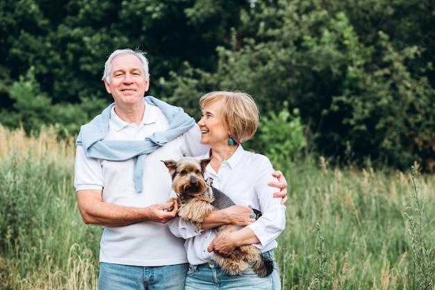 Пожилая пара гуляет с собакой в парке