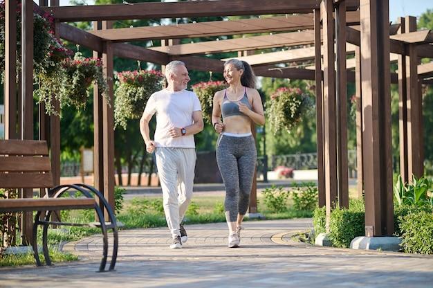 Пожилая пара бегает по парку и выглядит довольной