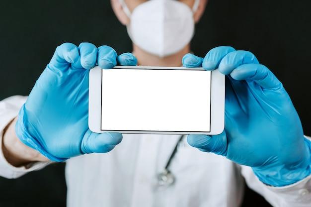 의료 마스크와 파란색 장갑에 성숙한 남성 의사는 그의 손에 스마트 폰을 보유하고 있습니다. 목업.
