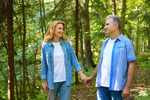 お互い手をつなぐ中年の男女が公園を歩いています。幸せな退職のコンセプト