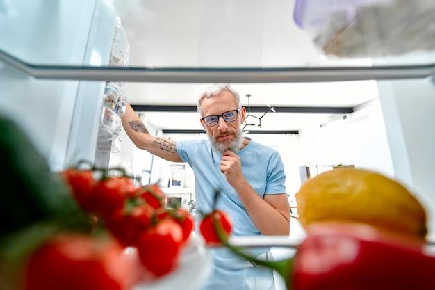 成熟した男が冷蔵庫を開けて何かを料理したり食べたりした。冷蔵庫からの眺め。