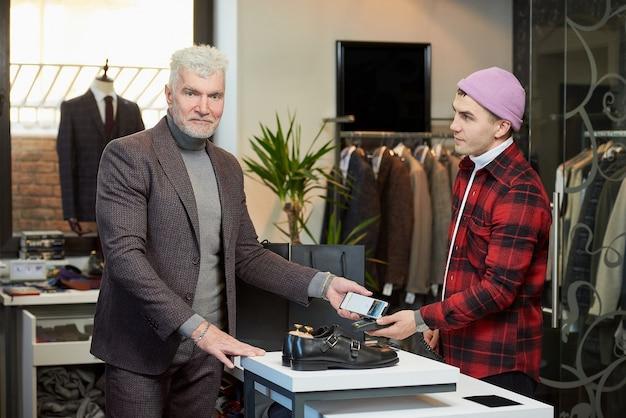 白髪でスポーティな体格の成熟した男性が、衣料品店のpos端末に携帯電話をかけています。あごひげを生やして満足している顧客がブティックの店員にお金を払っている