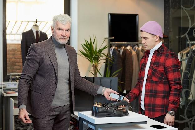 白髪でスポーティな体格の成熟した男性が、衣料品店のpos端末にスマートフォンを適用しています。あごひげを生やした男性客が、ブティックの店員にお金を払っています。
