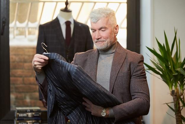 白髪でスポーティな体格の成熟した男性が衣料品店でウールのスーツをチェックしています。ブティックでひげを生やした男性客。