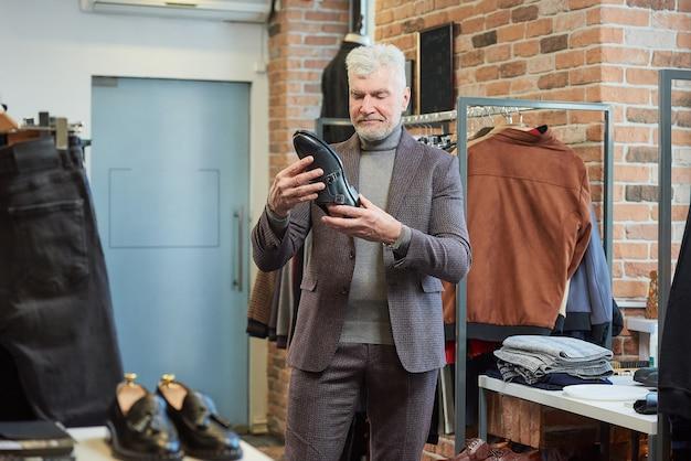 白髪でスポーティな体格の成熟した男性が衣料品店で靴を選んでいます。あごひげを生やした男性客がブティックでウールのスーツを着ている