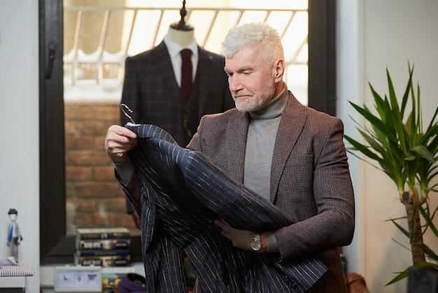 白髪でスポーティな体格の成熟した男性が、衣料品店でウールのスーツを調べています。ブティックでひげを生やした男性客。