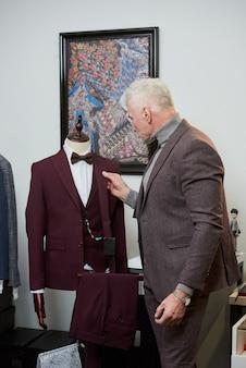 白髪でスポーティな体格の成熟した男性が、衣料品店のマネキンでウールのスーツを調べています。ブティックでひげを生やした男性客
