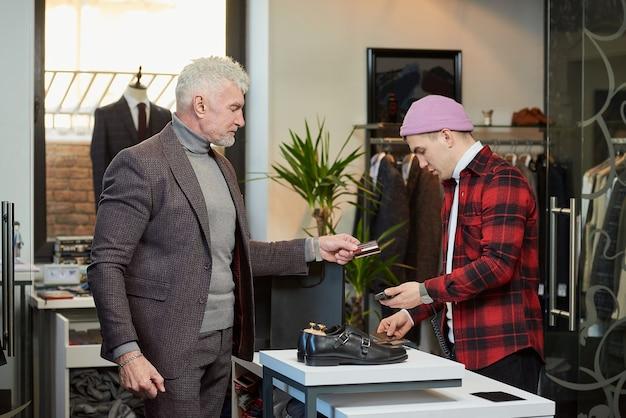 白髪でスポーティな体格の成熟した男性が、衣料品店での購入代金を支払うために売り手にクレジットカードを渡しています。あごひげを生やした男性客とブティックの店員。