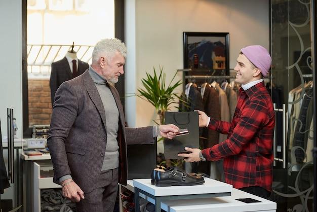 白髪でスポーティな体格の成熟した男性が、衣料品店での購入代金を支払うために売り手にクレジットカードを渡しています。笑顔の店員さんが男性客に紙袋を贈っています