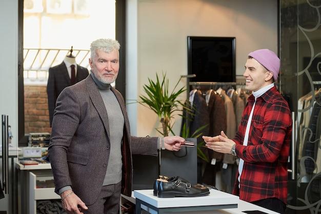 회색 머리카락과 스포티 한 체격을 가진 성숙한 남자가 옷가게의 웃는 판매자 근처에서 신용 카드를 들고 있습니다. 수염을 기른 남성 고객과 부티크에있는 점원.