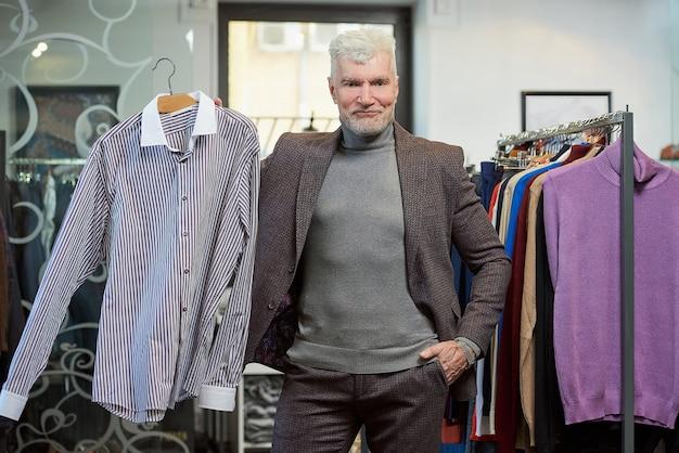 白髪でスポーティな体格の成熟した男性が、衣料品店でポーズをとってシャツを見せています。あごひげを生やした男性客は、ブティックでウールのスーツを着ています。
