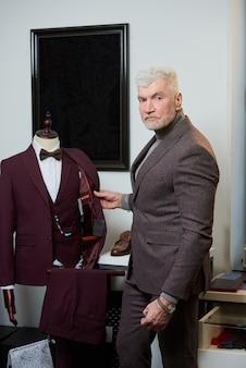 白髪でスポーティな体格の成熟した男性が、衣料品店のマネキンでウールのスーツを調べているときにポーズをとっています。ブティックでひげを生やした男性客