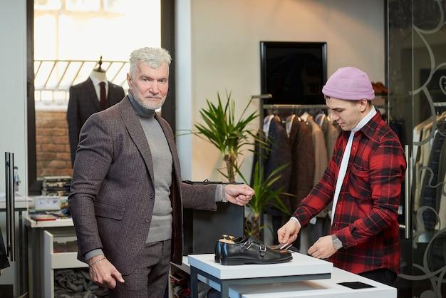 白髪でスポーティな体格の成熟した男性が、衣料品店での購入代金の支払い中にポーズをとっています。あごひげを生やした男性客とブティックの店員。