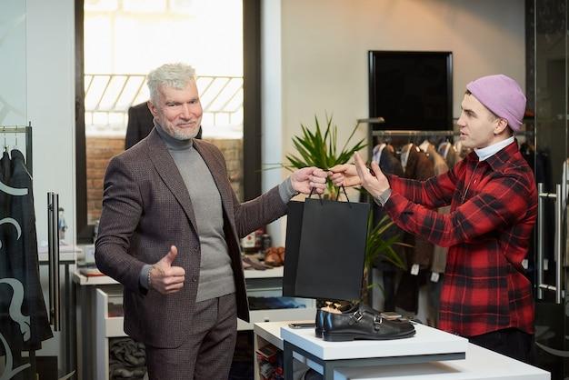 白髪でスポーティな体格の成熟した男性が、売り手から黒い紙袋を取り出し、衣料品店で親指を立てています。店員が男性客に紙袋を配っています。