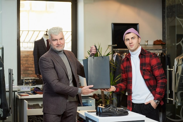 白髪でスポーティな体格の成熟した男性が、衣料品店の売り手から購入した黒い紙袋を持っています。満足している店員と男性客が紙袋でポーズをとっている