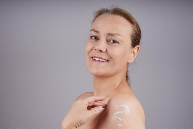 裸の肩を持つ成熟した笑顔の女性は彼女の肌にクリームを適用します。プロファイルの灰色の壁。フェイシャルスキンケアのコンセプト。