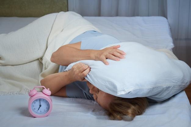 알람시계가 울려서 잠에서 깬 성숙한 여인이 베개로 머리를 가렸다. 부인은 불면증을 앓고 있습니다.