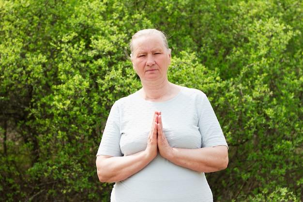 Зрелая женщина, одетая в белое, держится за руки, отдыхает после йоги в одиночестве по утрам. сосредоточен на расслаблении. концепция здорового образа жизни.
