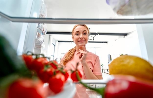 成熟した女性が何かを調理するために冷蔵庫を開けた。冷蔵庫からの眺め。