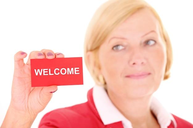 白い背景の上の赤いビジネスカードを持つ成熟した女性