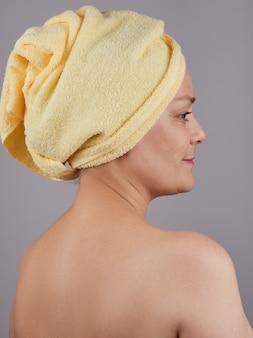 頭に黄色いタオルを持った成熟した女性が背中を背負って座っています。ボディスキンケアのコンセプト。灰色の壁に隔離