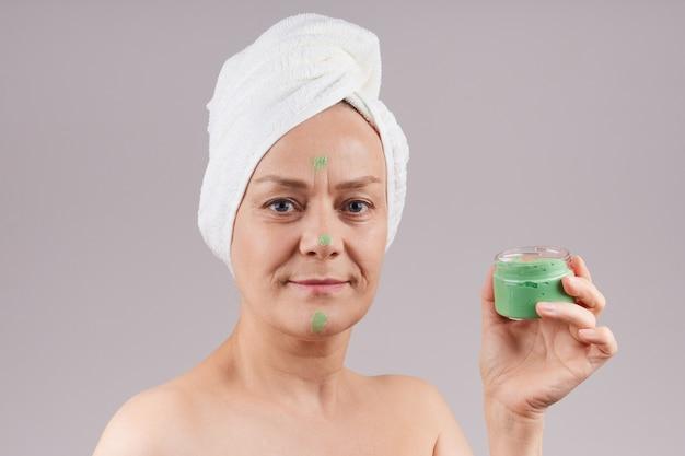 裸の肩、頭に白いタオル、緑色のフルーツクリームの瓶を持っている成熟した女性。フェイシャルスキンケアのコンセプト。灰色の壁を越えて。