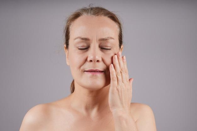 肩がむき出しの成熟した女性が、目を閉じて肌にクリームを塗ります。プロファイルの灰色の壁。フェイシャルスキンケアのコンセプト。