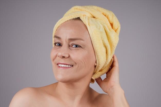 裸の肩と彼女の頭にタオルを笑顔の成熟した女性スキンケアのコンセプト。灰色の壁に隔離