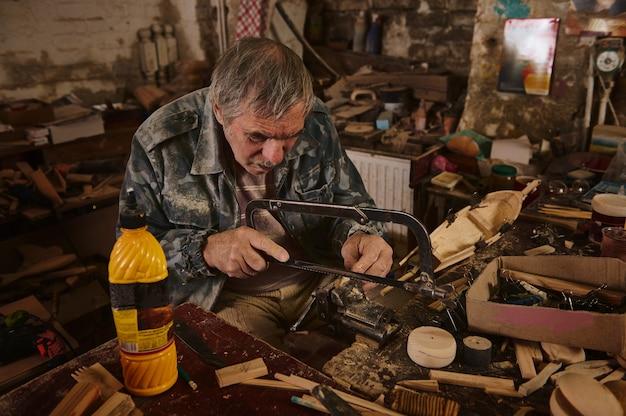 Зрелый мастер по дереву распиливает ножовкой кусок дерева, зажатый в тисках. ремесленник делает деревянные игрушки ручной работы. плотник в действии