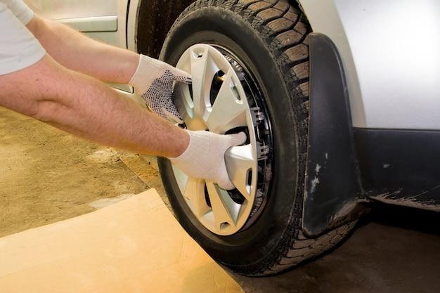 車のホイールからホイールキャップを取り外す整備士。タイヤフィッティング。タイヤサービス。