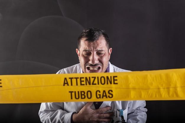 가스 누출 위기 동안 가스에 취한 의료 엔지니어. 노란 테이프에