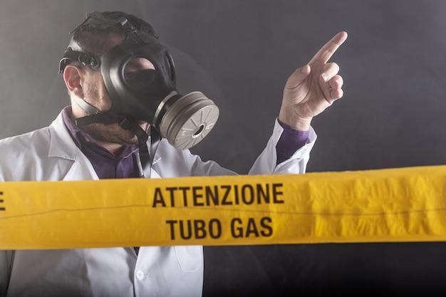 ガス漏れの危機を経験した防毒マスクを着用した医療技術者が、混乱の最中に緊急事態を指示しました。黄色いテープに「注意ガス管」と書かれた通知