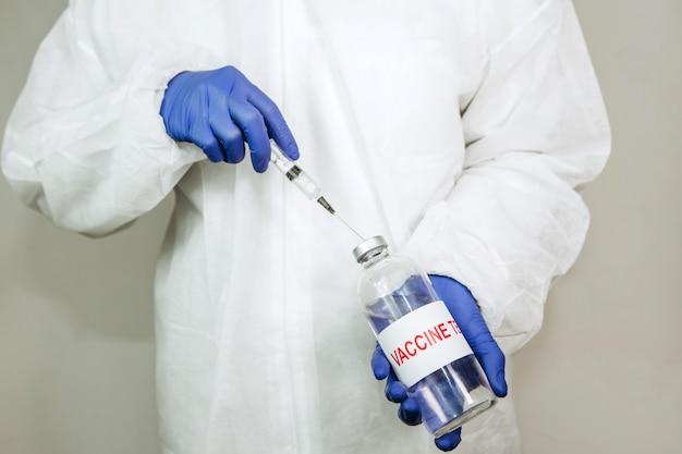 Работник медицинской лаборатории забирает вакцину в шприц. картез из ковид-2019. пандемия 2020 года. доктор в синих перчатках забирает лекарство в шприц. тестирование вакцины.