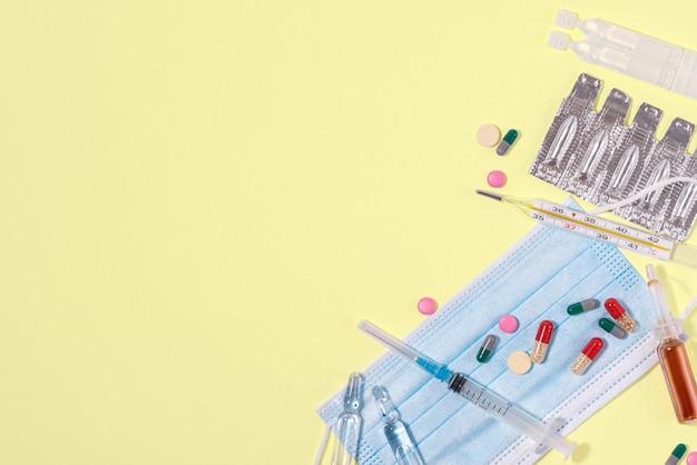 의료 마스크 주사기, 온도계 및 의약품은 노란색 배경 상단 보기에 놓여 있습니다