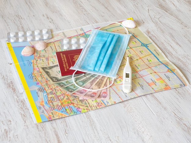 医療用マスク、地図、薬、パスポート、お金がテーブルに並べられています。旅行のコンセプト