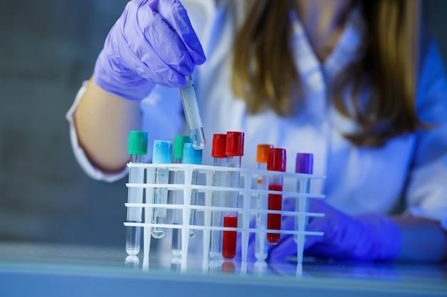 Медицинский работник, лаборант, врач выполняет анализ в лаборатории, использует пробирки, пипетку и чашку петри на наличие бактерий в организме человека.