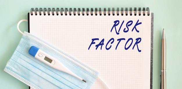 Медицинская защитная маска и градусник находятся на записной книжке с надписью о факторах риска в записной книжке.