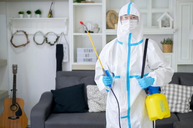 Ppeスーツの医療スタッフは、居間で消毒スプレーを使用しています。covid-19保護、消毒コンセプトです。