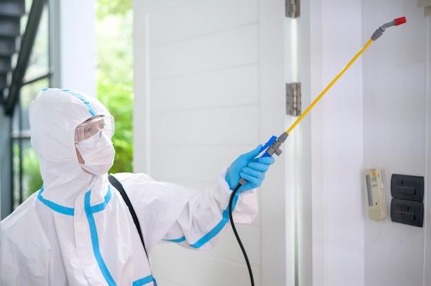 Ppeスーツの医療スタッフが居間で消毒スプレーを使用している、covid-19保護