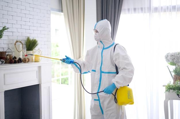 Ppeスーツの医療スタッフが居間で消毒スプレーを使用しています