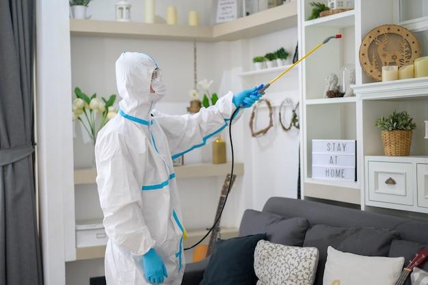 Ppe 정장을 입은 의료진이 거실에서 소독 스프레이를 사용하고 있습니다.