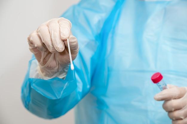 Медицинский работник, держащий комплект для сбора образцов тампона.