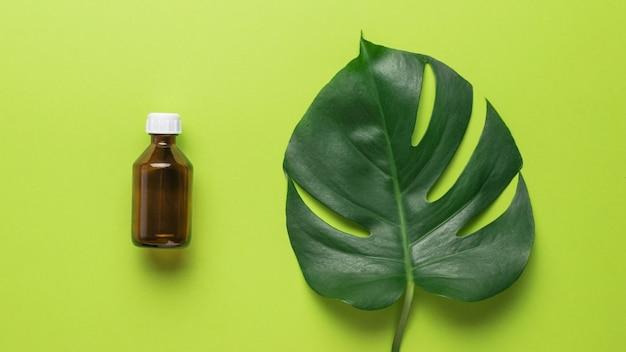 Бутылочка с лекарством с белой крышкой и зеленым листом монстера на зеленом фоне. плоская планировка.